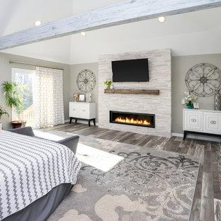 Diseño de dormitorio clásico renovado con paredes grises, suelo de madera en tonos medios, chimenea lineal, marco de chimenea de piedra y suelo gris
