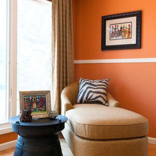 Bild på ett stort funkis huvudsovrum, med orange väggar och mellanmörkt trägolv