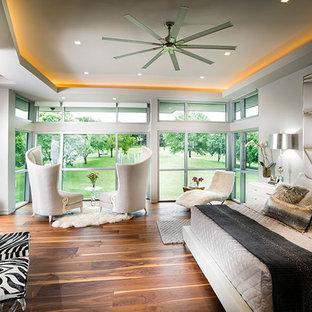 Imagen de dormitorio principal, actual, extra grande, con paredes grises, suelo de madera en tonos medios, chimenea de doble cara, marco de chimenea de piedra y suelo marrón