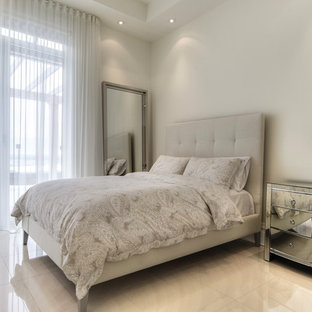 Mid-sized trendy guest marble floor and white floor bedroom photo in Montreal with white walls, a hanging fireplace and a plaster fireplace
