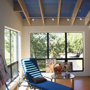 Ejemplo de habitación de invitados minimalista, pequeña, con paredes blancas y suelo de corcho