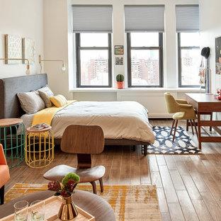 Ejemplo de dormitorio tipo loft, retro, pequeño, con paredes blancas, suelo de madera clara y suelo marrón