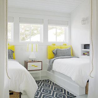 Cette image montre une petite chambre d'amis traditionnelle avec un mur blanc et un sol en bois peint.