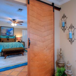 Diseño de dormitorio principal, vintage, con paredes beige y suelo de baldosas de terracota