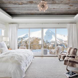 Uriges Schlafzimmer mit weißer Wandfarbe, Kamin, Kaminumrandung aus Stein, eingelassener Decke und Holzdecke in Sonstige