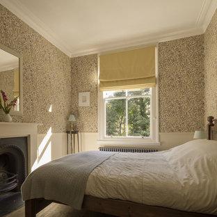 Inredning av ett klassiskt sovrum, med vita väggar, ljust trägolv, en standard öppen spis och en spiselkrans i metall