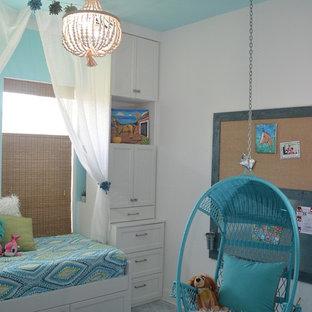 На фото: маленькая гостевая спальня в морском стиле с синими стенами, бетонным полом и белым полом