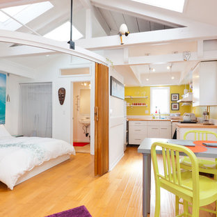 This is an example of an eclectic bedroom in Los Angeles with white walls, light hardwood floors and yellow floor.