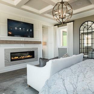 Großes Klassisches Hauptschlafzimmer mit grauer Wandfarbe, dunklem Holzboden, Tunnelkamin, Kaminumrandung aus Stein und grauem Boden in Los Angeles