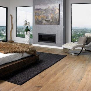 Example of a trendy master medium tone wood floor and brown floor bedroom design in Auckland with white walls and a standard fireplace