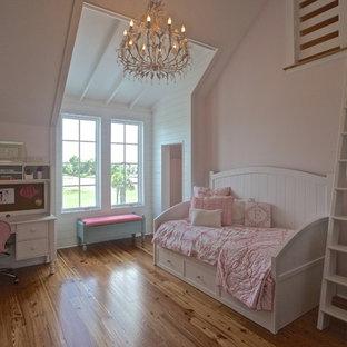 Modelo de dormitorio tipo loft, costero, sin chimenea, con paredes rosas y suelo de madera en tonos medios