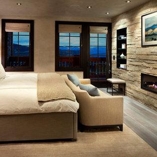 Foto de dormitorio principal, rústico, con paredes beige, suelo de madera oscura, chimenea lineal y marco de chimenea de piedra