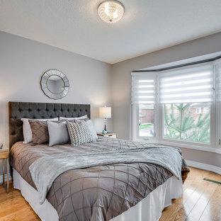 Immagine di una camera degli ospiti design di medie dimensioni con pareti grigie, parquet chiaro e pavimento giallo