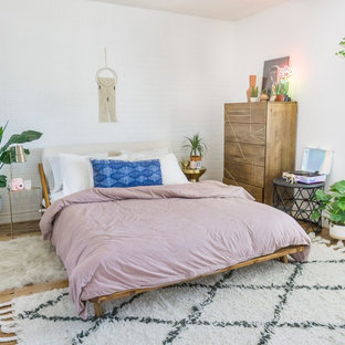 Example of a mid-sized eclectic master medium tone wood floor and brown floor bedroom design in Phoenix with white walls and a ribbon fireplace