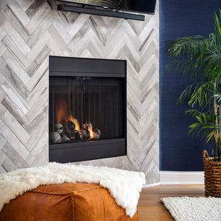Foto de dormitorio principal, costero, de tamaño medio, con paredes azules, suelo de madera clara, chimenea de esquina, marco de chimenea de baldosas y/o azulejos y suelo marrón