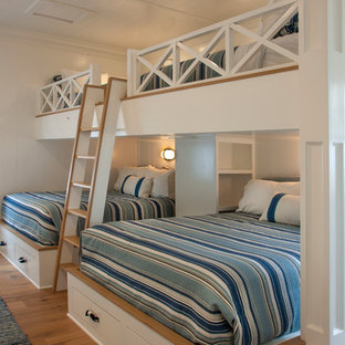 Design ideas for a beach style bedroom in San Diego with white walls, medium hardwood floors and brown floor.