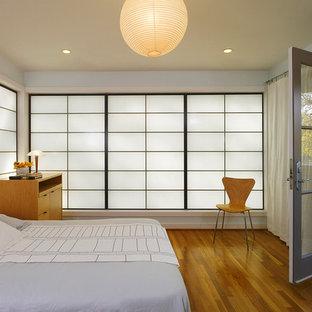 Idee per una camera matrimoniale moderna di medie dimensioni con pareti grigie, pavimento in legno massello medio, nessun camino e pavimento marrone