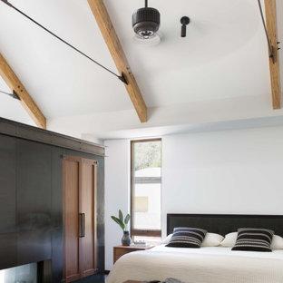 Modelo de dormitorio principal y abovedado, campestre, con chimenea de doble cara, marco de chimenea de metal, paredes blancas, suelo de cemento y suelo gris