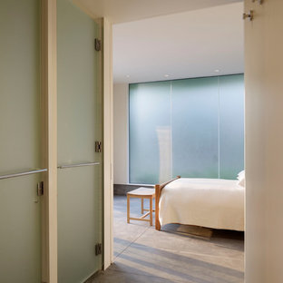 Design ideas for a mid-sized modern guest bedroom in San Francisco with concrete floors and white walls.