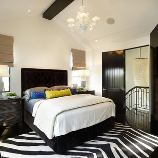 Mediterranean bedroom in Los Angeles with white walls, a corner fireplace, a stone fireplace surround and black floors.