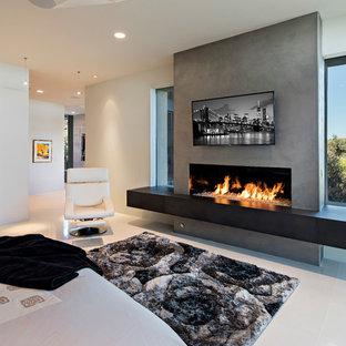 Imagen de dormitorio principal, minimalista, grande, con paredes beige, suelo de baldosas de porcelana, chimenea lineal y marco de chimenea de hormigón