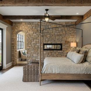 Imagen de dormitorio principal, clásico, con paredes grises, suelo de madera oscura, chimenea de doble cara y marco de chimenea de piedra