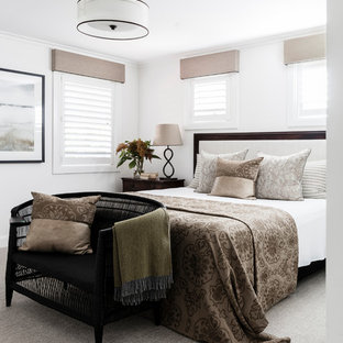 This is an example of a classic bedroom in Sydney with white walls, carpet and grey floors.