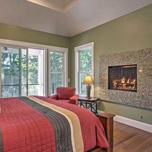 Diseño de dormitorio principal, marinero, grande, con paredes verdes, suelo de madera clara, chimenea tradicional y marco de chimenea de piedra