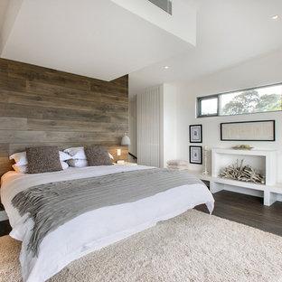 Modelo de dormitorio cama en frente a ventana, contemporáneo, con paredes blancas y suelo de madera oscura