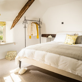 Medium sized rural master bedroom in Devon with white walls and carpet.