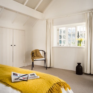 Mid-sized scandinavian master bedroom in Devon with white walls and carpet.