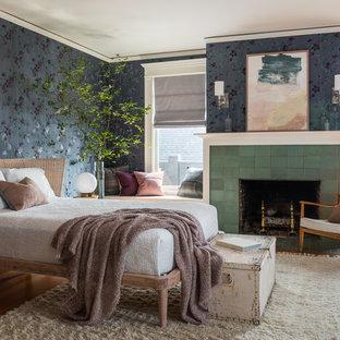 Exempel på ett mellanstort amerikanskt huvudsovrum, med flerfärgade väggar, mellanmörkt trägolv, en standard öppen spis, en spiselkrans i trä och brunt golv
