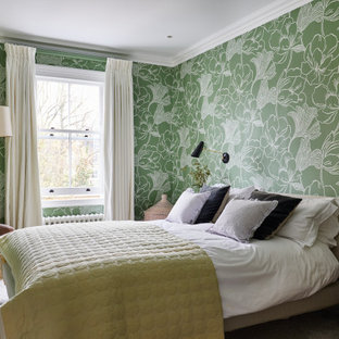 Inspiration for a transitional master bedroom in London with green walls, medium hardwood floors, brown floor and wallpaper.
