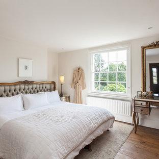 Esempio di una camera da letto classica di medie dimensioni con pareti bianche, pavimento in legno massello medio e pavimento marrone