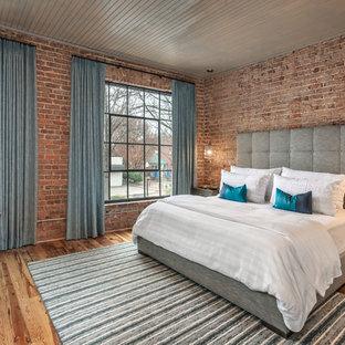 Imagen de habitación de invitados industrial, grande, con paredes rojas, suelo de madera en tonos medios y suelo marrón