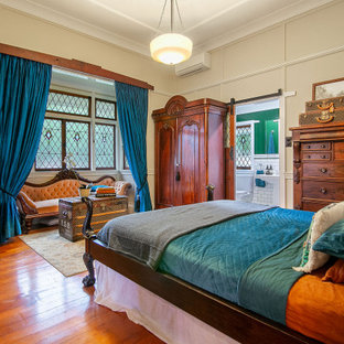 Inspiration for a traditional bedroom in Brisbane with beige walls, medium hardwood floors, brown floor and panelled walls.