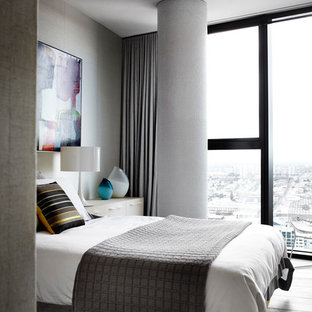 Photo of a mid-sized modern loft-style bedroom in Melbourne with grey walls, medium hardwood floors and no fireplace.