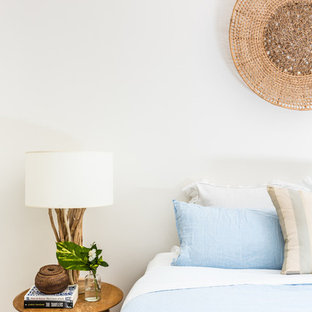 Inspiration for a large beach style master bedroom in Melbourne with white walls and carpet.
