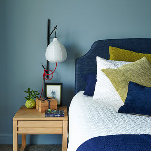 This is an example of a mid-sized contemporary master bedroom in Melbourne with blue walls, carpet and grey floor.