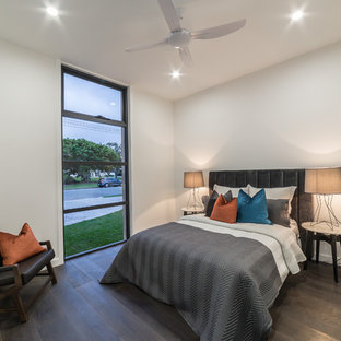 This is an example of a contemporary guest bedroom in Gold Coast - Tweed with white walls, medium hardwood floors, no fireplace and brown floor.