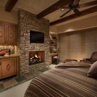 Idéer för ett mellanstort amerikanskt gästrum, med beige väggar, skiffergolv, en standard öppen spis och en spiselkrans i sten