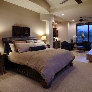 フェニックスの大きいサンタフェスタイルのおしゃれな主寝室 (石材の暖炉まわり、コーナー設置型暖炉、ベージュの壁、トラバーチンの床、茶色い床) のインテリア