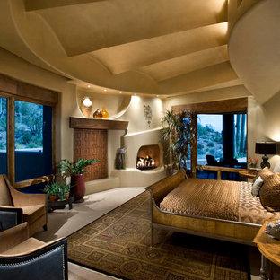 На фото: большая хозяйская спальня с бежевыми стенами, ковровым покрытием, стандартным камином, фасадом камина из штукатурки и серым полом с