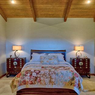 Diseño de dormitorio principal, campestre, con paredes beige, suelo de piedra caliza, chimenea de esquina, marco de chimenea de yeso y suelo blanco