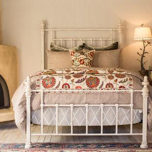 Esempio di una camera degli ospiti american style di medie dimensioni con pareti beige, pavimento in legno verniciato, camino ad angolo e cornice del camino in intonaco