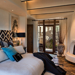 フェニックスの中サイズのサンタフェスタイルのおしゃれな主寝室 (ベージュの壁、漆喰の暖炉まわり、濃色無垢フローリング、コーナー設置型暖炉、茶色い床) のレイアウト
