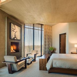 Imagen de dormitorio principal, contemporáneo, de tamaño medio, con paredes beige, moqueta, chimenea tradicional, suelo beige y marco de chimenea de hormigón