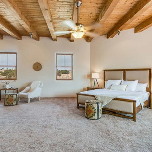 Inspiration for a large master bedroom in Other with beige walls, brick floors, no fireplace and brown floor.