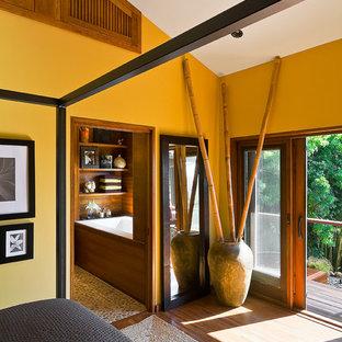 サンタバーバラの中サイズのコンテンポラリースタイルのおしゃれな主寝室 (黄色い壁、無垢フローリング、暖炉なし、茶色い床)