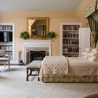 Inspiration for a timeless master bedroom remodel in New York with beige walls, a standard fireplace and a stone fireplace